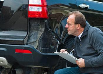 man checking damaged car